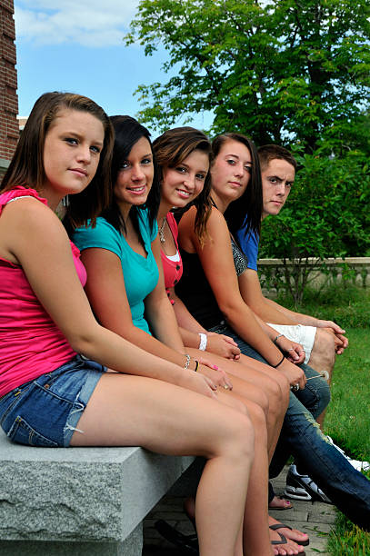 Group of Students Waiting on a Bench stock photo