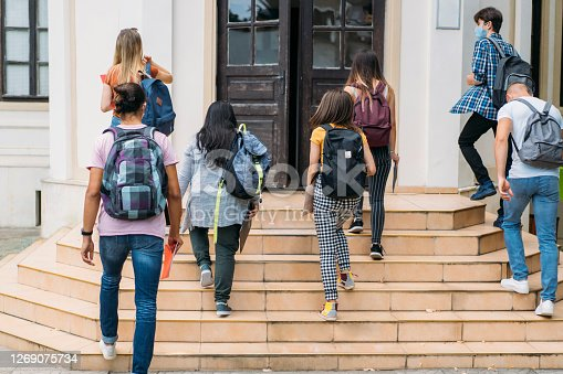 Group of students walking in college, they wearing protective face masks.