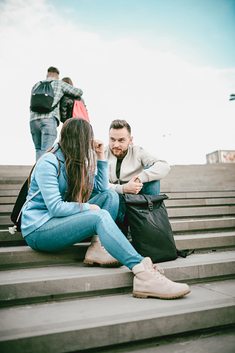 872670290 istock photo Group of Students with Backpacks Sitting and Talking on Stairs and Boy and Girl are Skipping Class 929907430