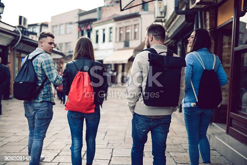 872670290istockphoto Group of Students with Backpacks Walking After School 909209148