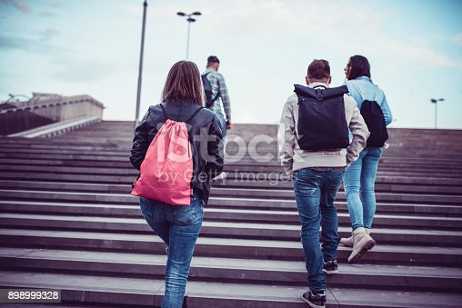 872670290istockphoto Group of Students with Backpacks Walking to School 898999328