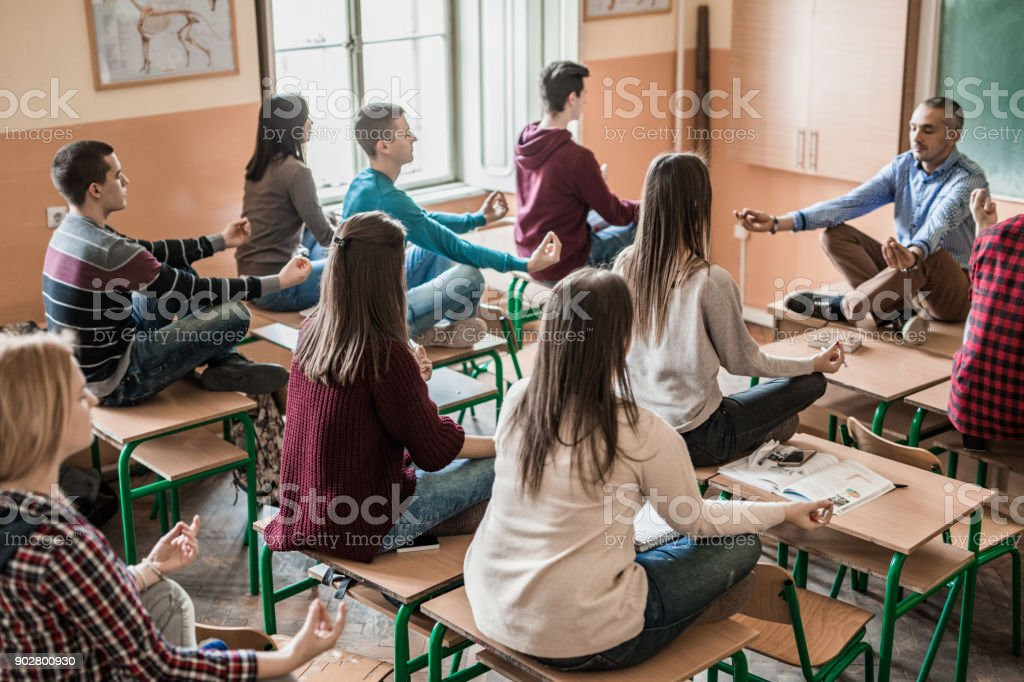 Group of students with their professor meditating in the classroom. stock photo