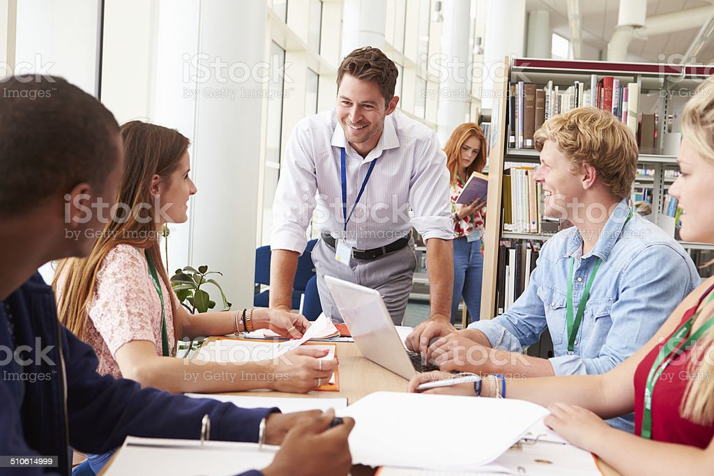 Group Of Students Working Together In Library With Teacher stock photo