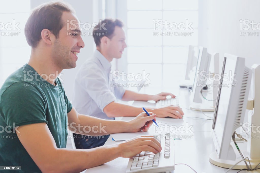 group of students working with computers stock photo
