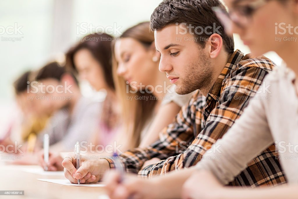 Group of students writing during a lecture. stock photo