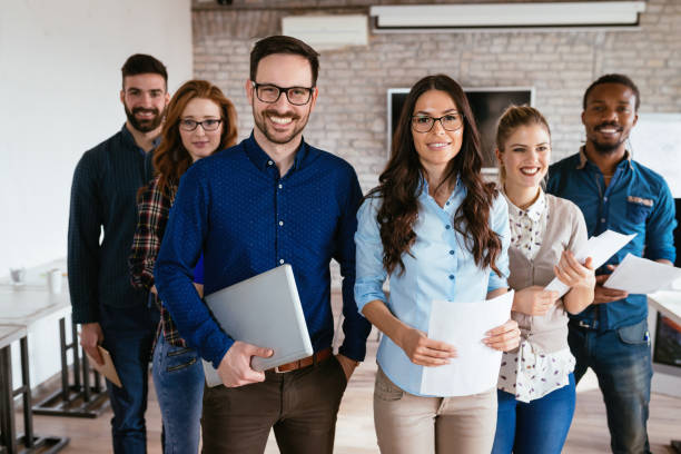 Group of successful young architects posing in office stock photo