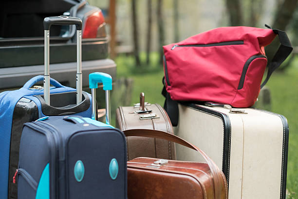 Group of suitcases next to the trunk. stock photo