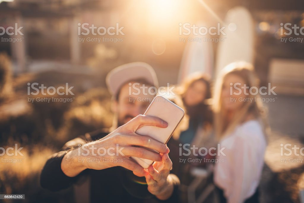 Group of surfers making selfie stock photo