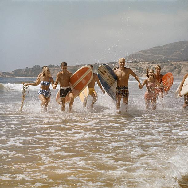 grupo de surfistas correndo na água com pranchas de surfe, sorrindo - com os pés na água - fotografias e filmes do acervo