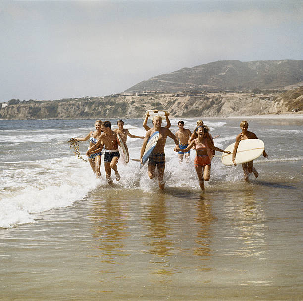 group of surfers running in water with surfboards, smiling - archival stock photos and pictures