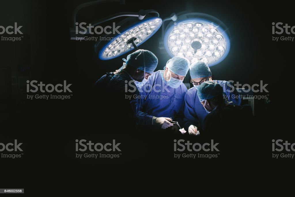 Group of surgeons at work in operation theater. stock photo