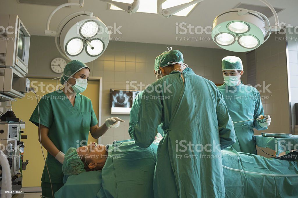 Group of surgeons working on a female patient royalty-free stock photo