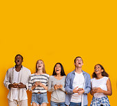 istock Group of surprised students with smartphones over yellow background 1199669971
