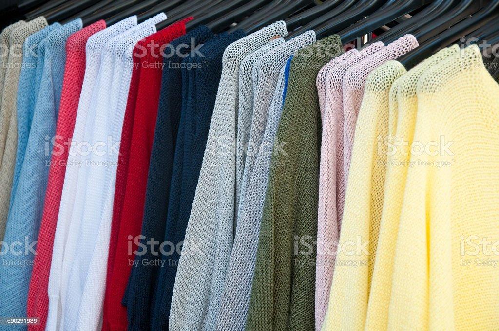 group of sweaters of all colors hanging Стоковые фото Стоковая фотография