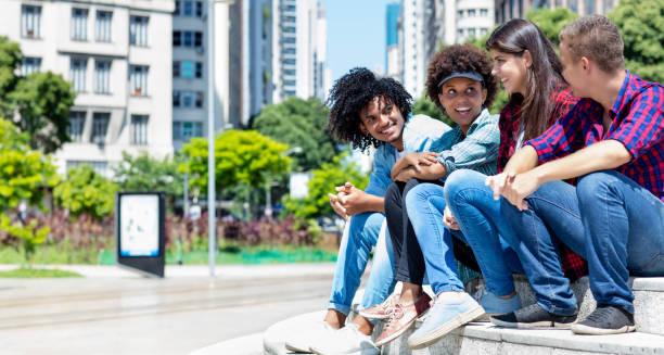 Grupo de jóvenes hipsters parlantes en la ciudad - foto de stock