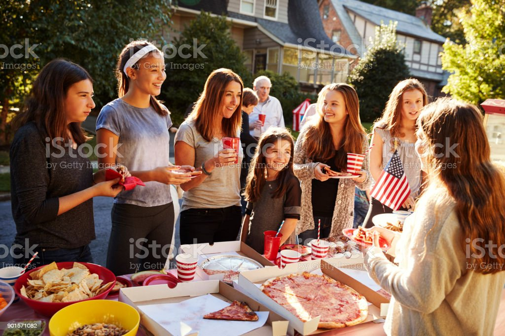 Group of teen girls talking over food table at a block party stock photo