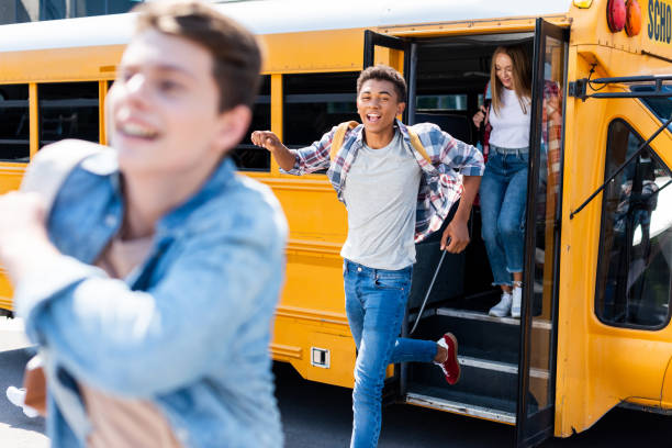 group of teen students running out of school bus - school bus stock photos and pictures