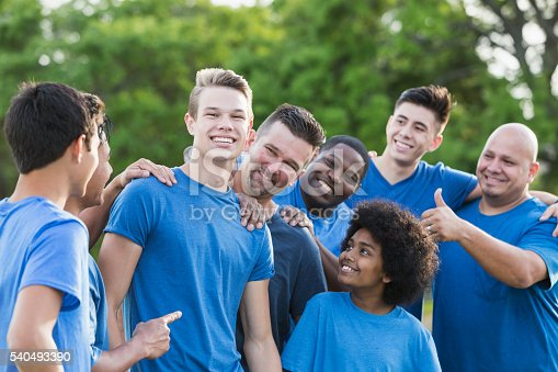 istock Group of teenage boys and fathers wearing blue shirts 540493390