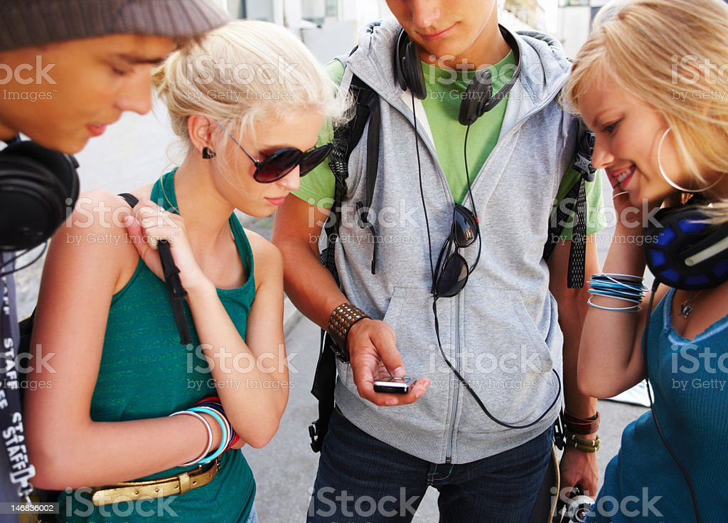 Group of teenage boys and girls looking on cellphone royalty-free stock photo