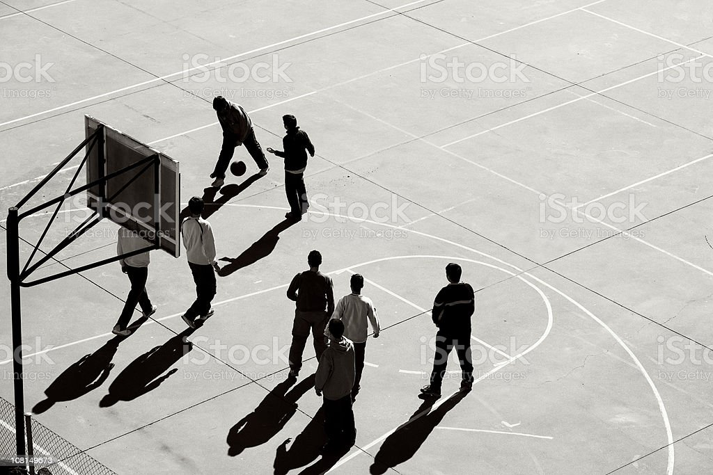 Group of Teenage Boys Playing Basketball on Outdoor Court stock photo