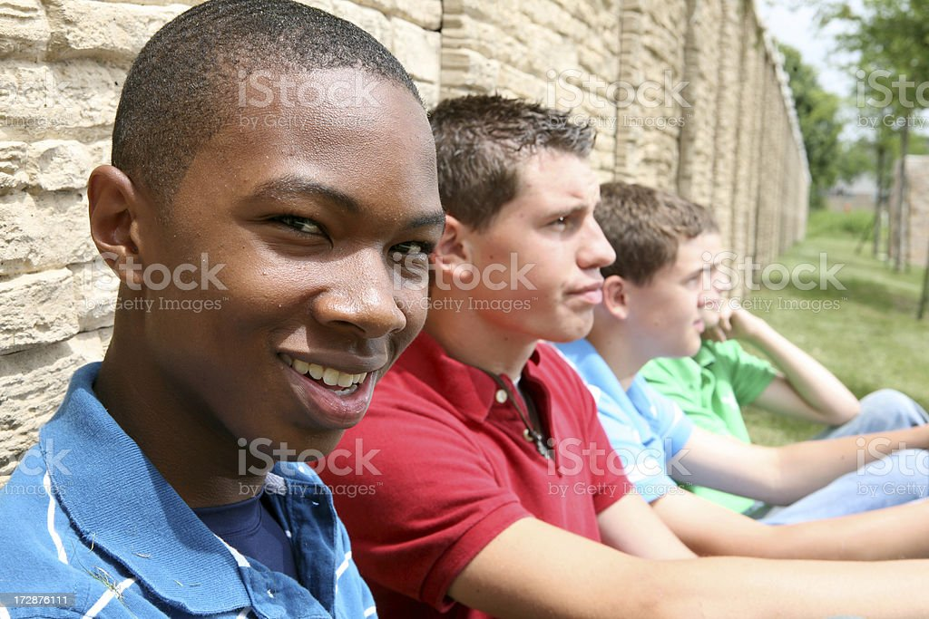Group Of Teenage Boys Sitting By A Wall royalty-free stock photo