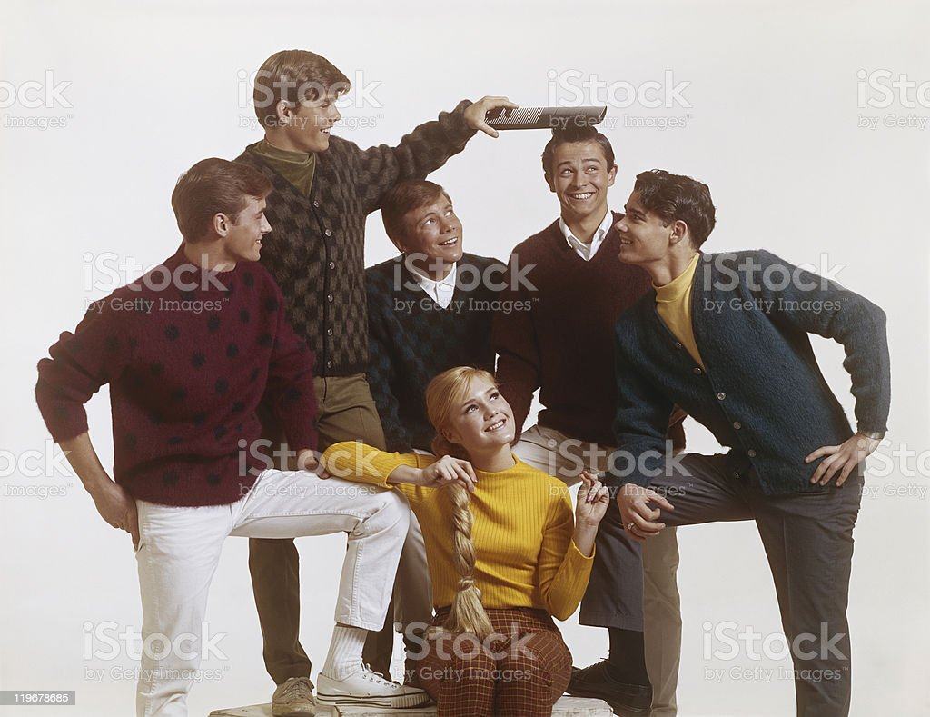 Group of teenage boys with girl, boy combing friend's hair with big comb royalty-free stock photo