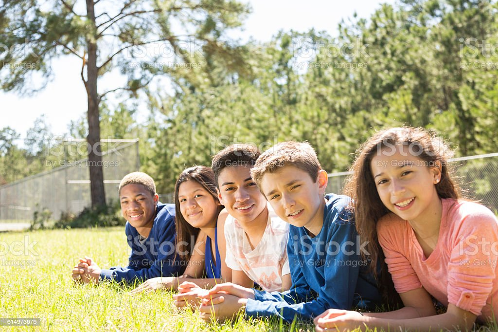 Group of teenage friends hang out together at park, campus. stock photo