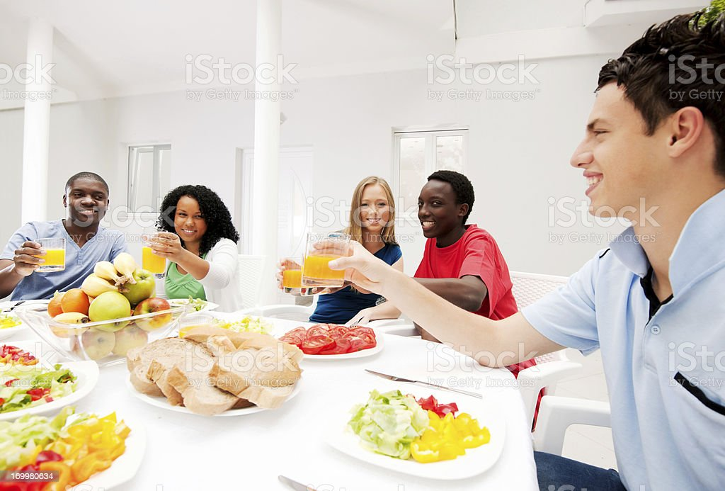 Group of teenage friends having dinner outdoors. royalty-free stock photo