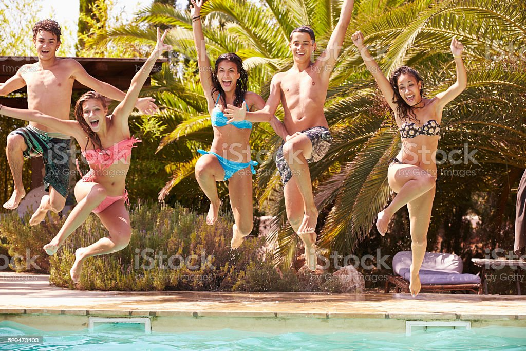 Group Of Teenage Friends Jumping Into Swimming Pool stock photo