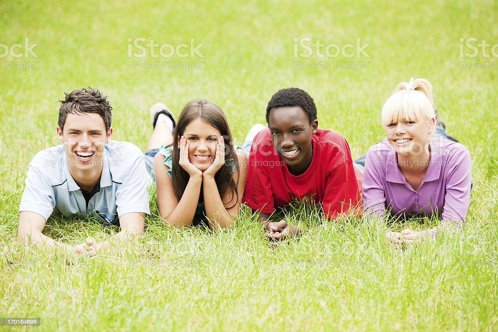 Group of teenage friends lying in the grass. royalty-free stock photo
