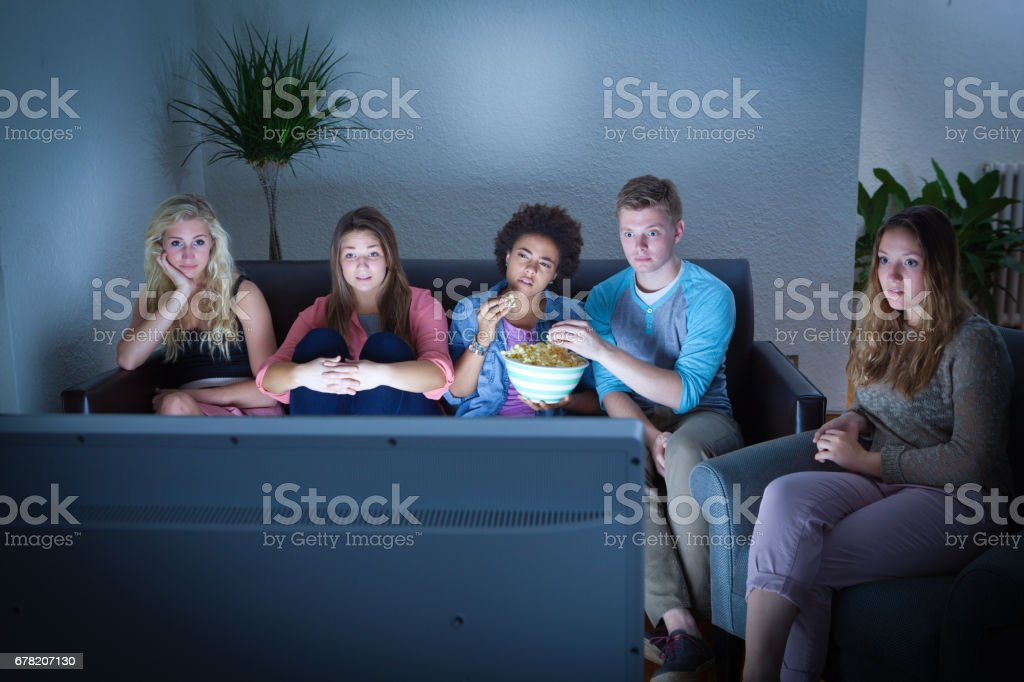 Group of Teenage Girls and Boys Watching Together in Front of a TV stock photo