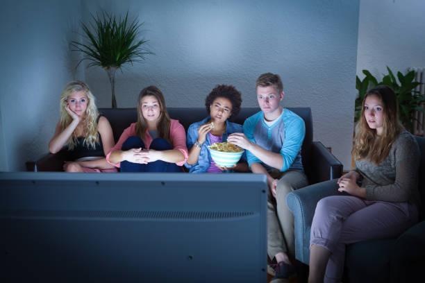 gruppe von mädchen und jungen gemeinsam vor dem fernseher beobachten - mädchen night snacks stock-fotos und bilder
