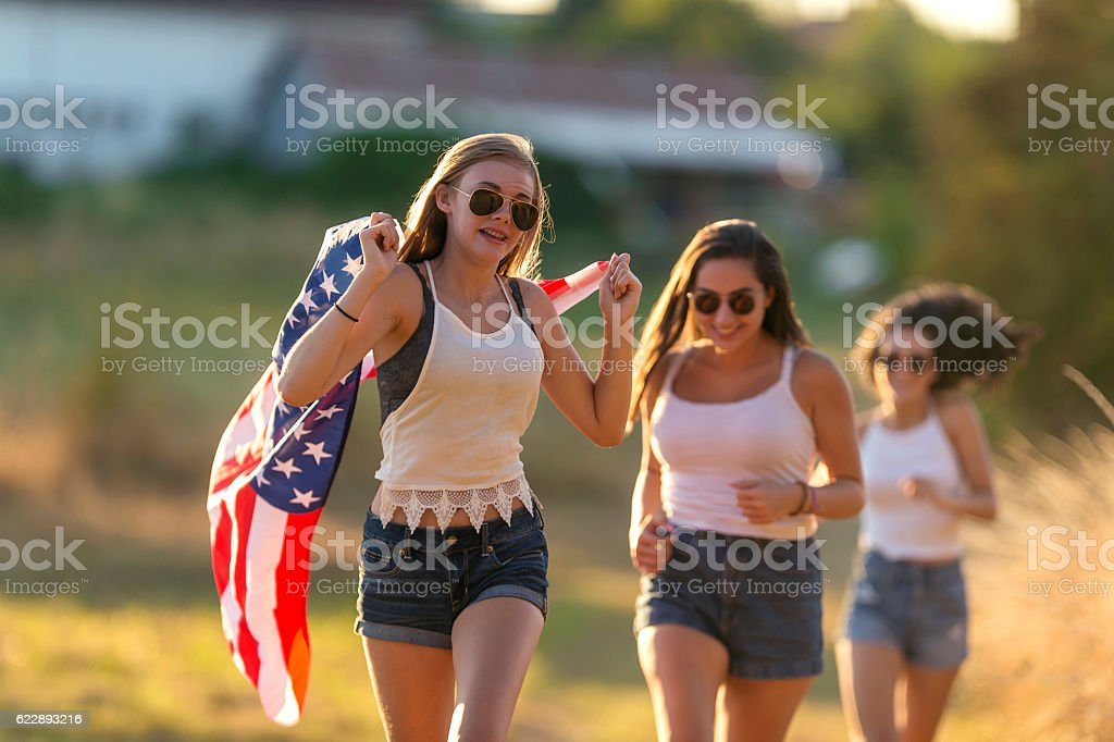 Group of teenage girls running with an American flag stock photo