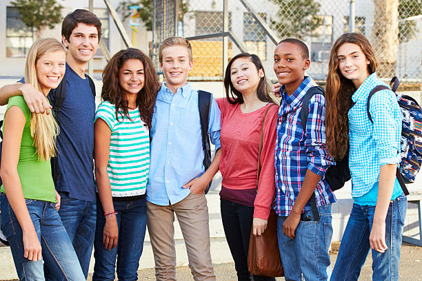 Group Of Teenage Pupils Outside Classroom Group Of Teenage Pupils Outside Classroom With Arms Round Each Other Smiling At Camera pre adolescent child stock pictures, royalty-free photos & images