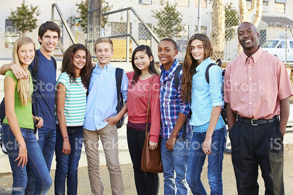 Group Of Teenage Pupils With Teacher Outside Classroom stock photo