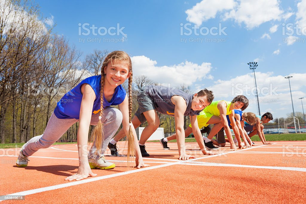 Group of teenage runners lined up ready to race stock photo
