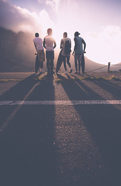Group of teenage skater friends at sunset stock photo