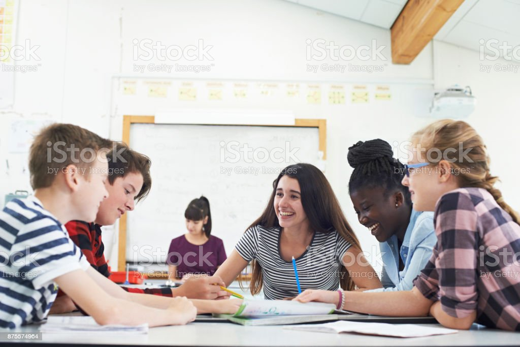 Group Of Teenage Students Collaborating On Project In Classroom stock photo