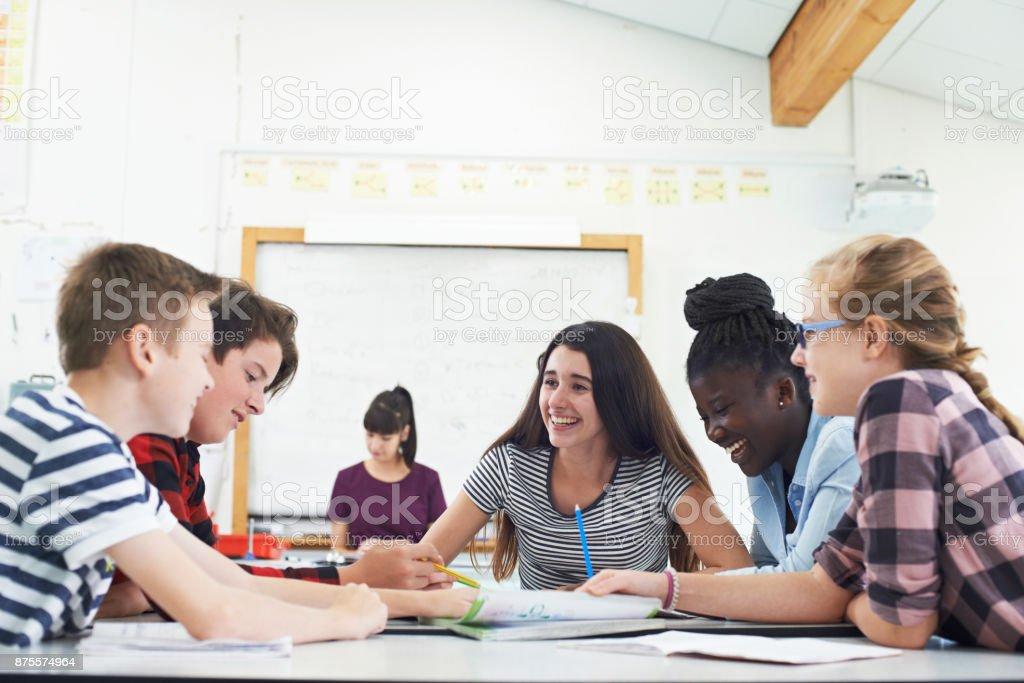 Grupo de adolescentes estudiantes colabora en proyecto de aula - foto de stock