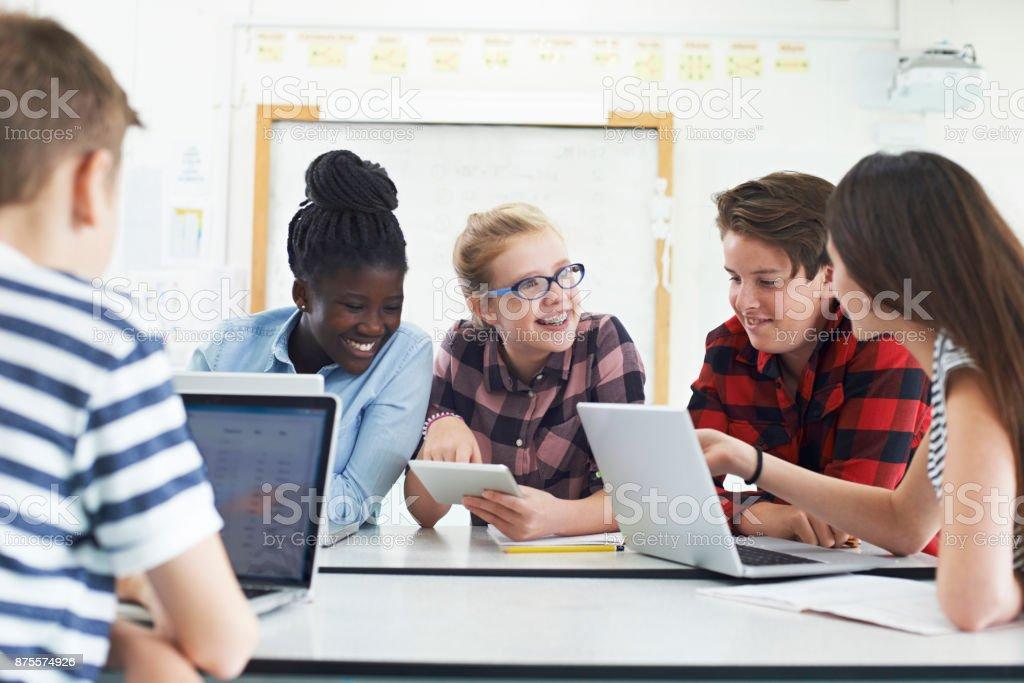 Grupo de adolescentes estudiantes colaboran en proyecto en clase de informática - foto de stock