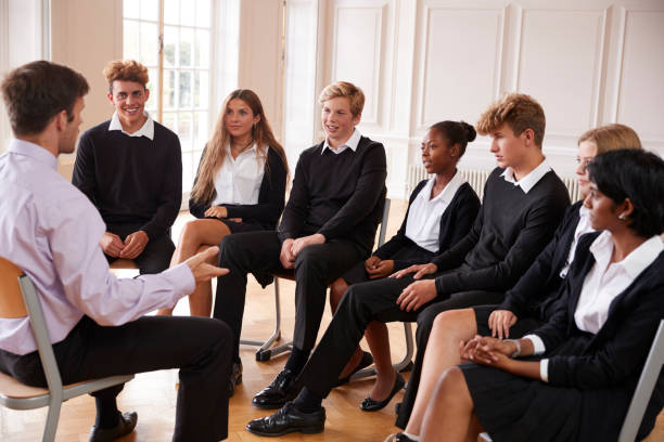 group of teenage students having discussion with tutor - private school stock photos and pictures