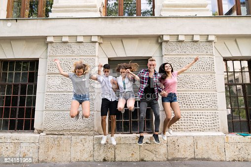 824257318 istock photo Group of teenage students in front of university jumping high. 824151958