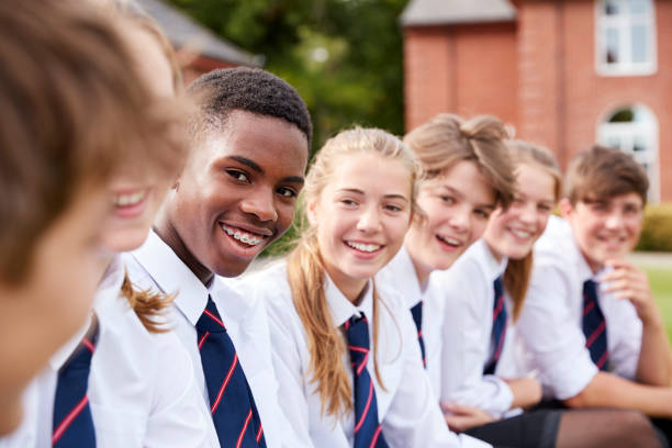 group of teenage students in uniform outside school buildings - private school stock photos and pictures