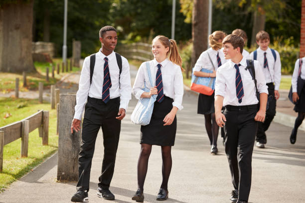 group of teenage students in uniform outside school buildings - uniform stock photos and pictures