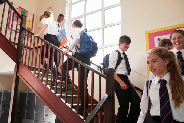 group of teenage students in uniform walking between classrooms - private school stock photos and pictures