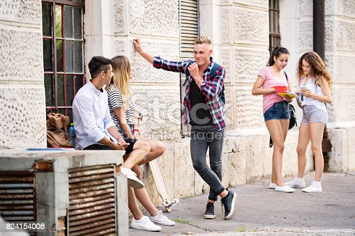 824257318 istock photo Group of teenage students talking in front of university. 824154008
