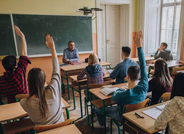 group of teenage students with raised arms in the classroom. - professore di scuola superiore foto e immagini stock