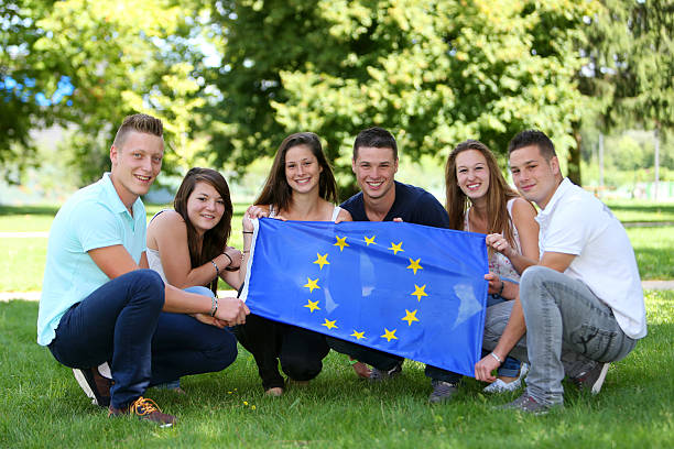 Group of teenagers and Flag Group of teenagers with the European flag ecole stock pictures, royalty-free photos & images