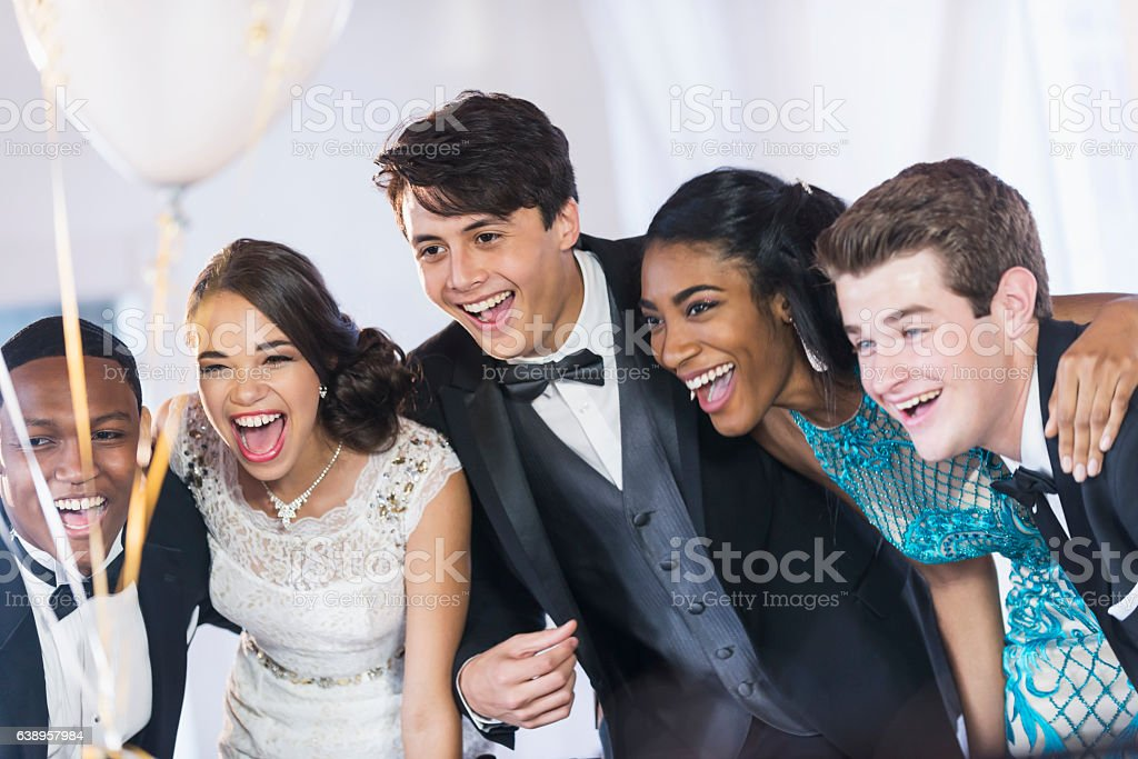 Group of teenagers at party wearing gowns and tuxedos - foto de stock