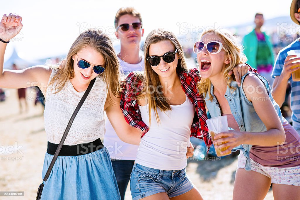 Group of teenagers at summer music festival, sunny day stock photo